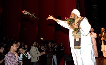 Shaykh Babikir throwing roses into the audience